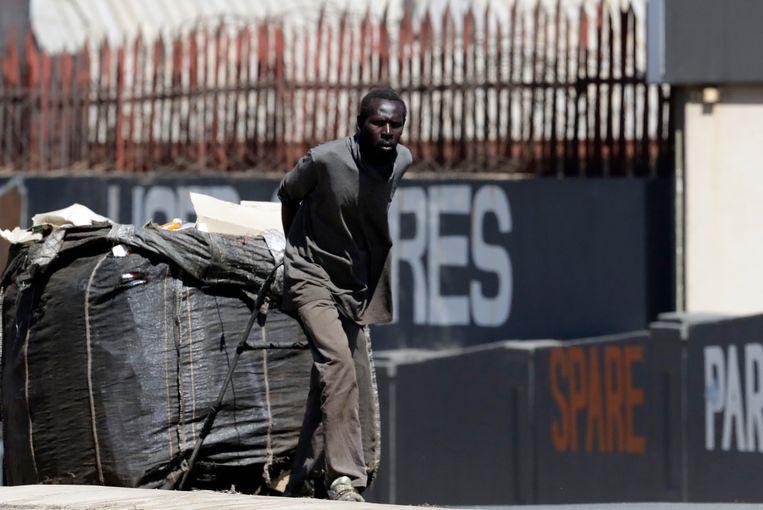 Een werkloze man in Johannesburg trekt een karretje vol recyclebaar afval bedoeld voor verkoop. Beeld AP