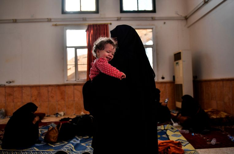 De echtgenote van een vermoedelijk strijder van IS houdt haar kind stevig vast nadat ze wist te ontsnappen uit Raqqa.