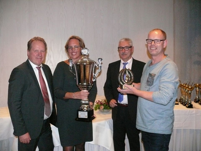 Yvonne Jurriens (met beker) en Marco Jurriens (met beeldje bronzen rookworst) hebben de prijzen voor de beste rookworst overhandigd gekregen.