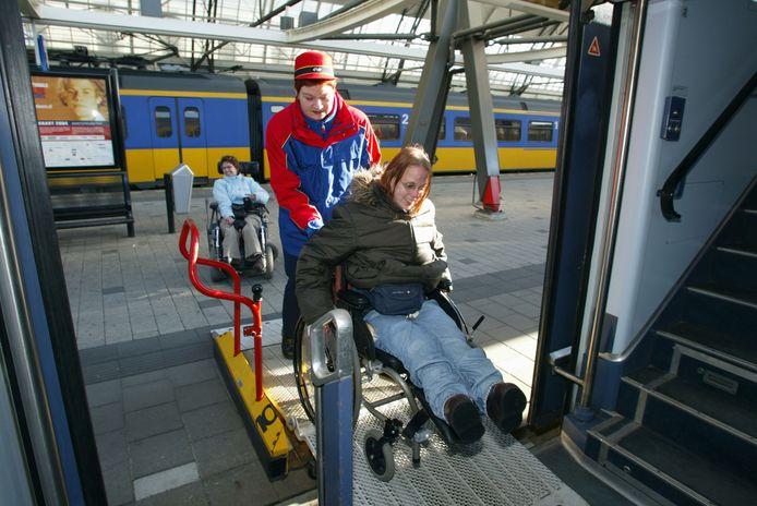 Een vrouw met beperking wordt door een NS-medewerker de trein in geholpen