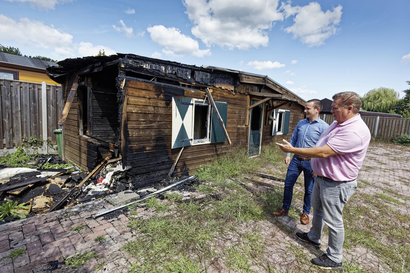 Peter van Boxtel en woordvoerder Joeri van Duuren van EuroParcs bij de restanten van het chalet dat in juli uitbrandde.