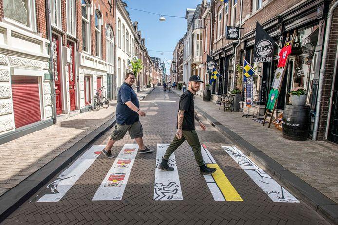 Nee hoor *kuch* natuurlijk weten ondernemers Olivier Jaspers (links) en Max de Jong niks van het zebrapad tussen hun zaken. De gemeente kan in ieder geval wel om de guerrilla-actie lachen.
