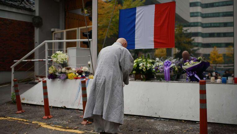 Een boeddhistische monnik bidt voor de slachtoffers in Parijs bij de Franse ambassade in Seoul Beeld AP