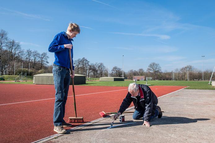 Sisu pleegt groot onderhoud aan de atletiekbaan. Deze foto met vrijwilligers Thomas Mijnders en Henk Meenhuis is van enkele jaren terug.