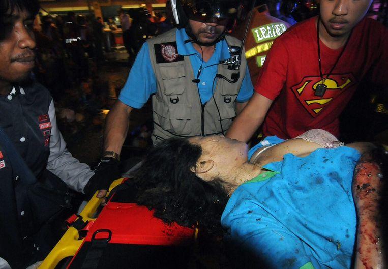 Thaise reddingswerkers helpen een gewonde vrouw na de aanslag in de buurt van het Erawan-schrijn in Bangkok.
