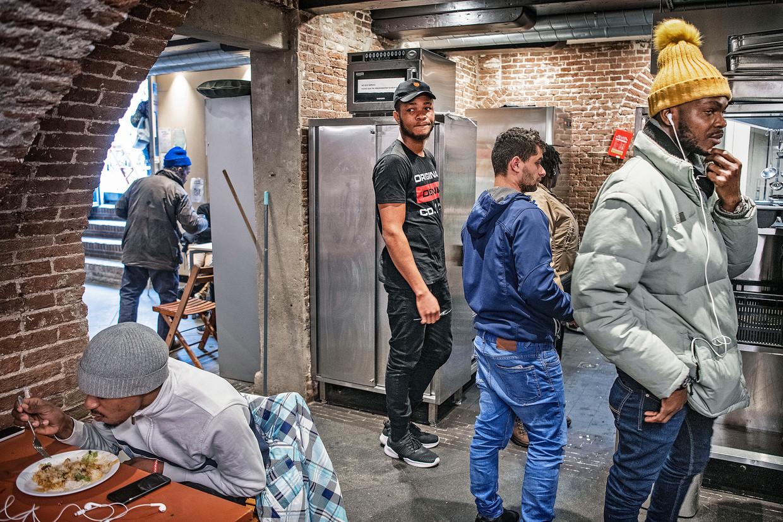 Daklozen wachten donderdag in het Wereldhuis op een maaltijd, voorlopig hun laatste.  Beeld Guus Dubbelman / de Volkskrant