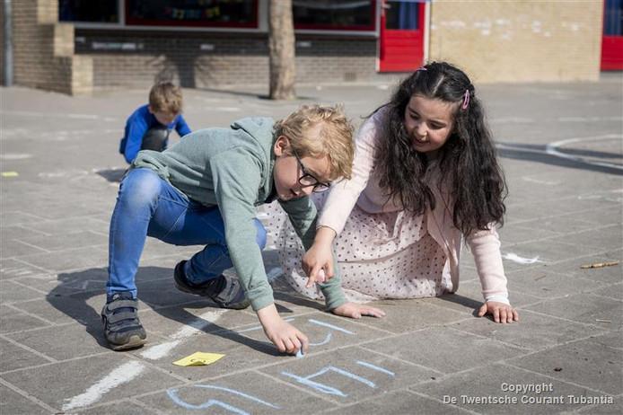 Leerlingen van Daltonschool 't Schöppert maken buiten, op de speelplaats, de rekensommen.