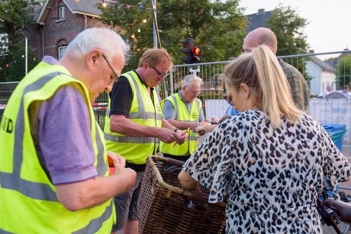 Enkele leden van de MMP plakken een nummertje op de fiets van een van de vele kermisgangers in Zeelst.