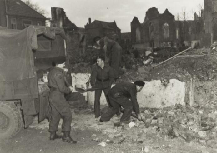Canadese soldaten ruimen na de bevrijding puin in de binnenstad van Doetinchem. Op de achtergrond zijn de contouren te zien van de verwoeste Catharinakerk. De foto is gemaakt vanuit de Waterstraat.