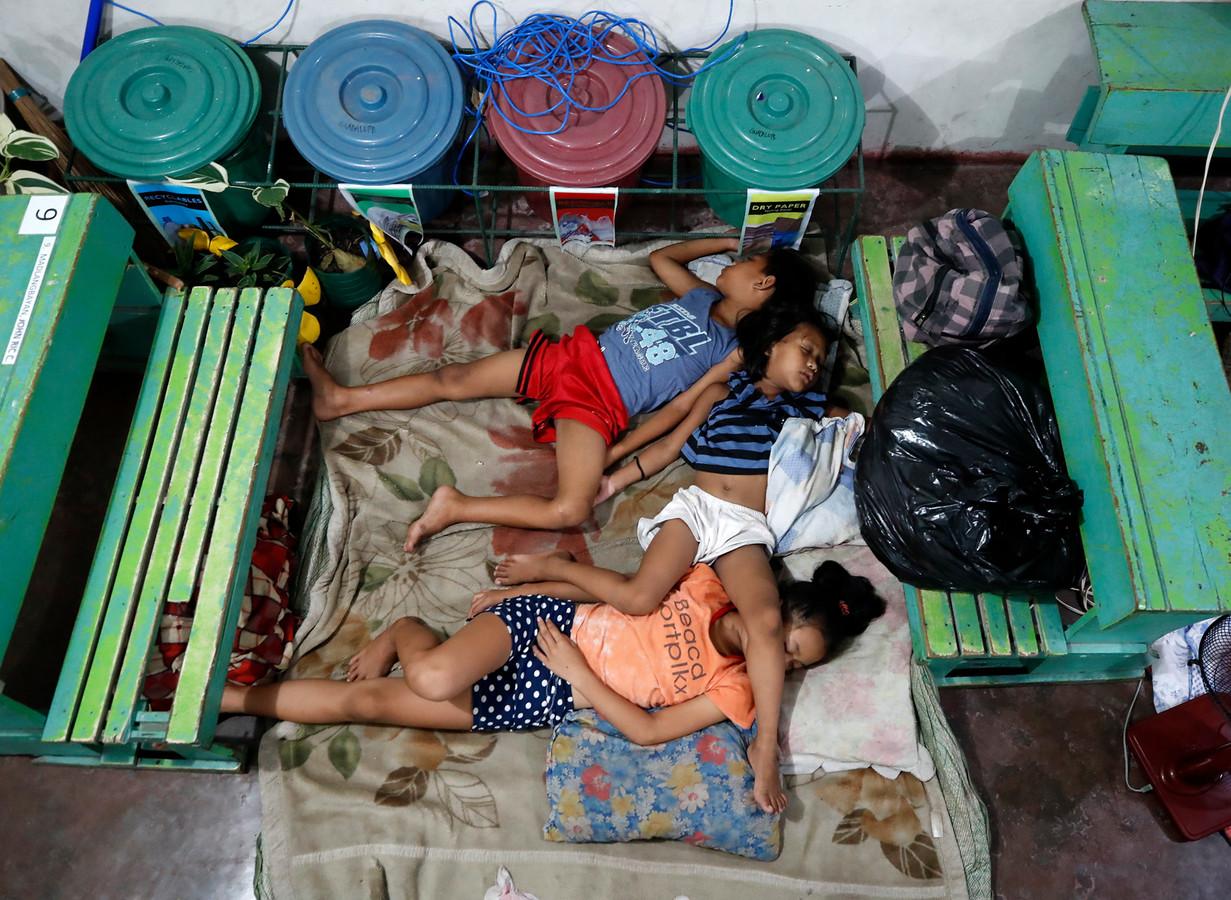 Geëvacueerde families overnachten in een schoolgebouw.