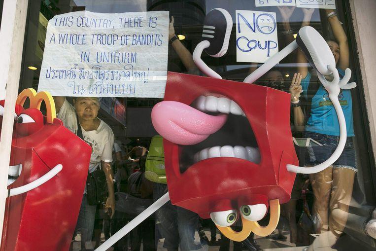 Thaise betogers schuilen in een McDonald's tijdens een demonstratie tegen de coup van het leger Beeld getty