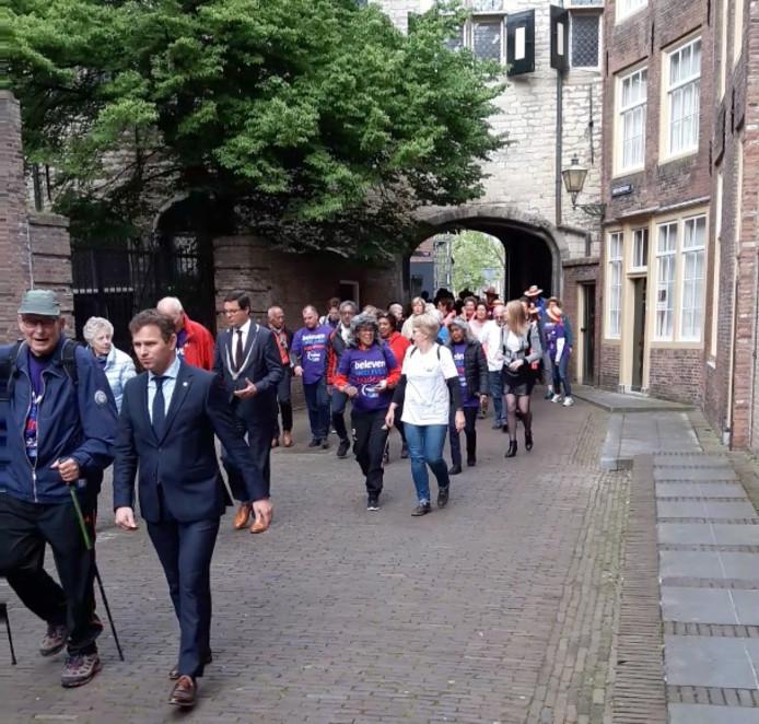 Lopers door de poort bij het Damplein in Middelburg