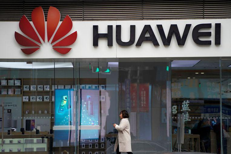Een vrouw wandelt voorbij een winkel van Huawei in Shanghai.