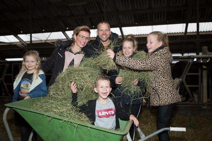 Harold Dubbink, zijn vrouw Petra en de kinderen, met hooi als voer voor zijn 85 melkkoeien.