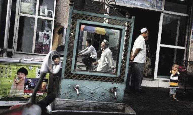 Oeigoeren voor een restaurant in Kashgar, in de Chinese provincie Xinjiang. Met steun van de Sovjet-Unie werd tweemaal, in 1933 en 1944, de Oeigoerse Republiek van Oost-Turkestan uitgeroepen. In 1949 annexeerden de Chinese communisten het gebied. Hun vrees voor Oeigoers seperatisme zijn de Chinezen nooit kwijtgeraakt. (FOTO AP) Beeld