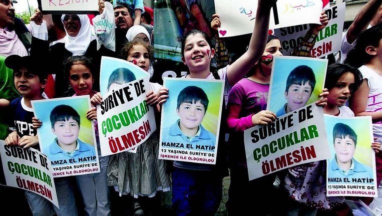 Syrische kinderen demonstreren met posters van de vermoorde 13-jarige Hamza bij het Syrische consulaat in Istanbul. Beeld