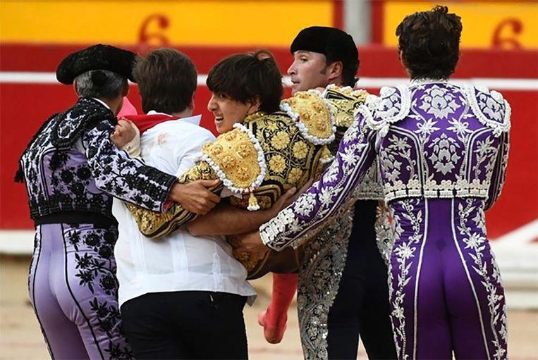 De gewonde stierenvechter wordt uit de arena gedragen.