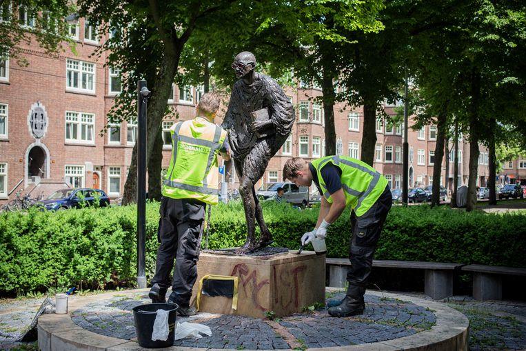 Medewerkers van de Stichting Standbeeld Mahatma Gandhi verwijderen de verf van het bekladde Gandhi-beeld. Beeld Maarten Brante
