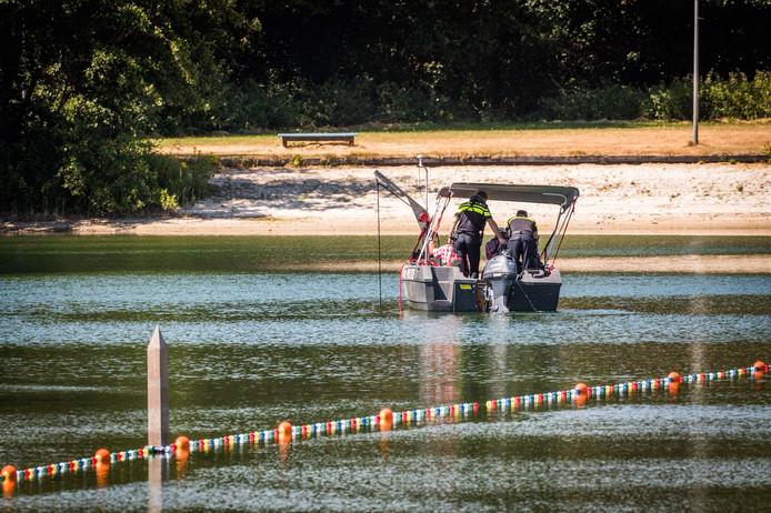 Specialisten zoeken op een specifieke plek in het strandbad in Nuenen.