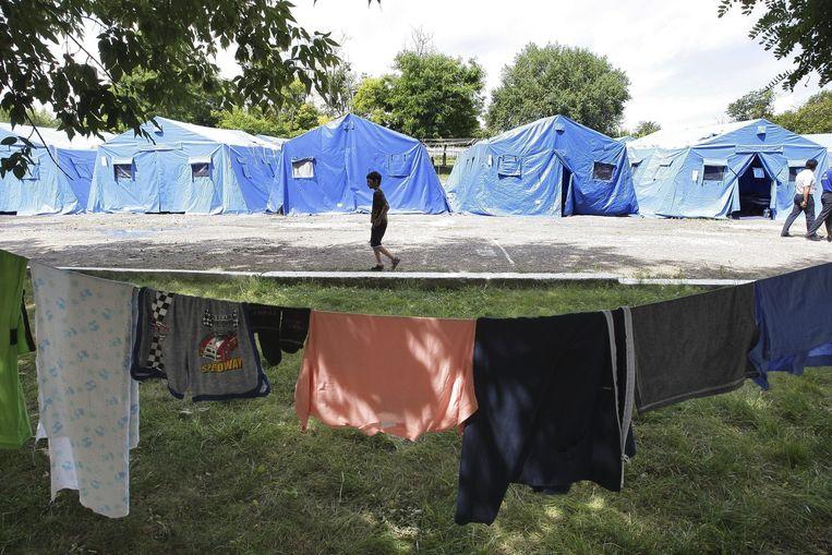 Een Oekraïense jongen loopt langs tenten in een vluchtelingenkamp in Simferopol op de Krim. Beeld epa