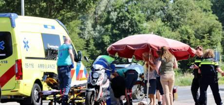 Omstanders zorgen met parasol voor schaduw na valpartij met brommer in Oldenzaal