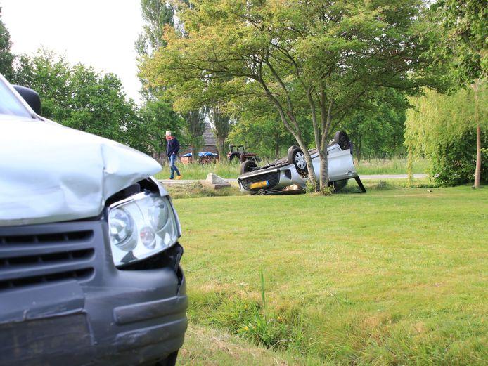 De auto van de vrouw ligt op de kop bij een boom, de beschadigde bestelbus op de voorgrond.