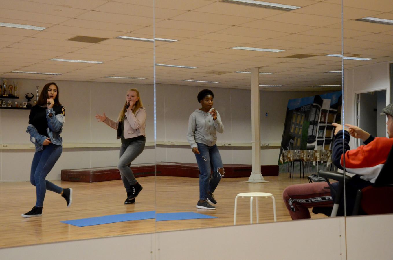 Oefenen voor Tilburg's Got Talent. In de spiegel van links naar rechts: Isa, Farah en Favour. Vooraan in de stoel: dansdocent Mark Snels geeft aanwijzingen.