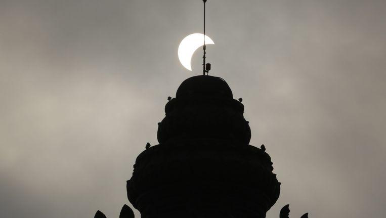 Een gedeeltelijke zonsverduistering boven het onafhankelijkheidsmonument in Phnom Penh. Beeld epa
