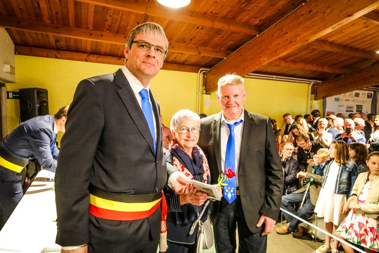 Burgemeester Patrick Lansens (sp.a, links) overhandigt Monique Delrue en Urbain Scharmin hun trouwboekje, net in het weekend dat ze 50 jaar getrouwd zijn.