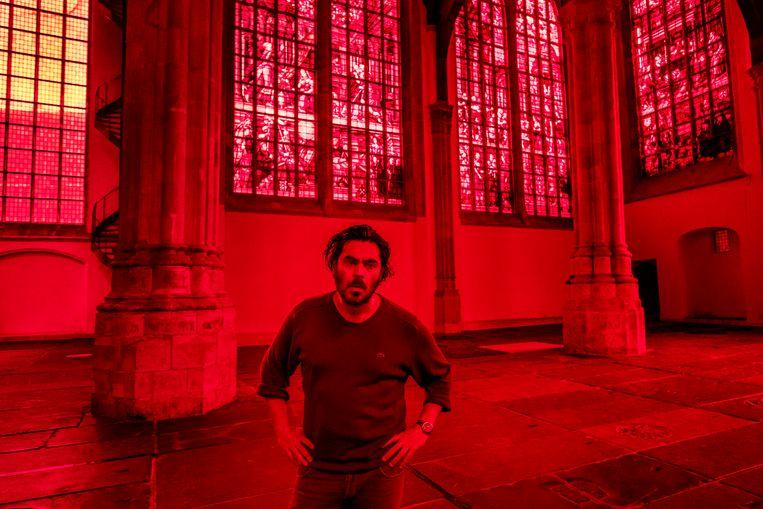 De Italiaanse kunstenaar Giorgio Andreotta Calò beplakte de ramen van de Oude Kerk in Amsterdam met rode folie en plexiglas: 'Zo wil ik de geschiedenis van deze kerk zichtbaar maken voor de bezoeker'. Beeld Patrick Post