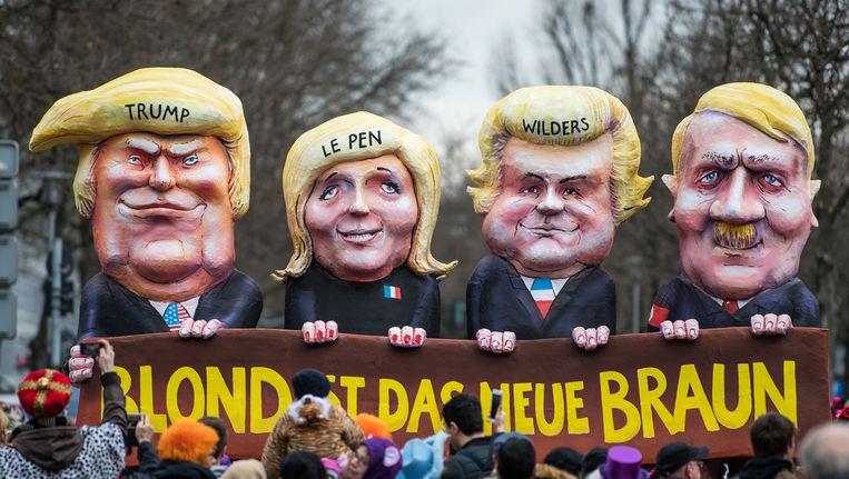 Een praalwagen met Wilders, Le Pen, Trump en Hitler tijdens de carnavalsoptocht in Düsseldorf. 'Blond is het nieuwe bruin', luidt de tekst eronder. 'Ziek', vind Wilders. Beeld getty