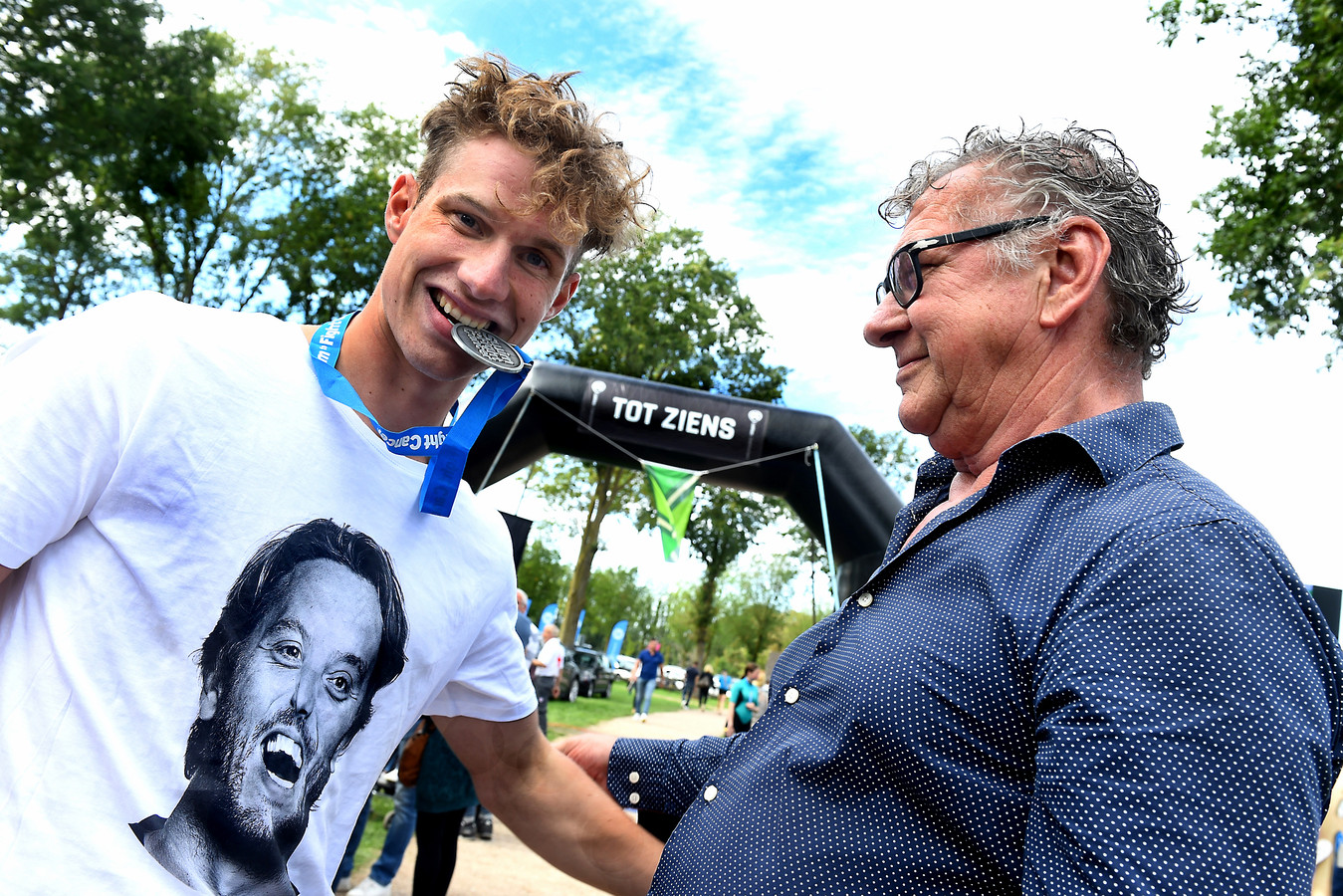 Deelnemer Noud van de Louw en zijn vader vieren de geslaagde zwemtocht Swim to Fight Cancer. ,,Dat krijg je dan, de ene traan lokt de andere uit.''