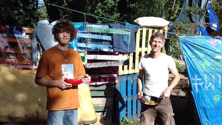 Larch en zijn zoon Seb bij het zelfgebouwde dorpje waar tientallen activisten in de bomen wonen. Beeld Patrick van IJzendoorn