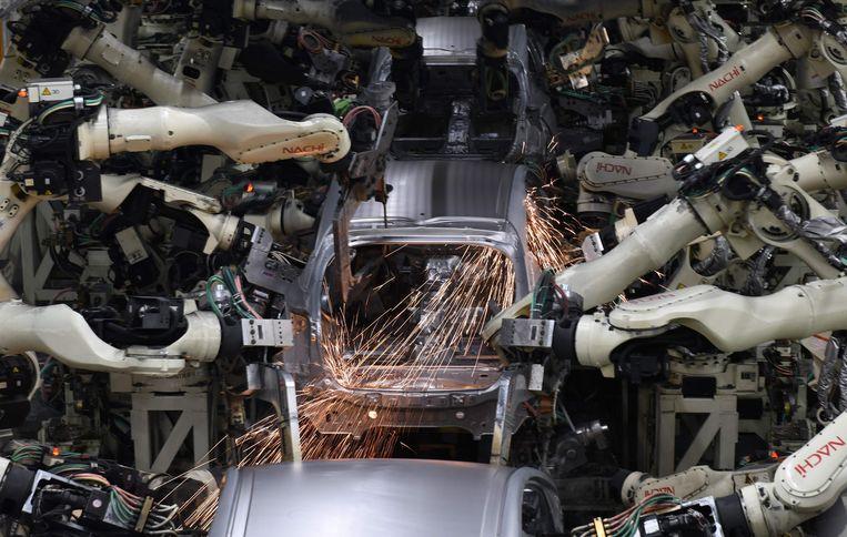 Robotarmen bezig met laswerkzaamheden aan een Toyota Prius. Er komt geen mens meer aan te pas. Beeld AFP