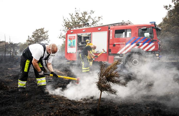 foto ter illustratie. Brandweerlieden blussen na bij een natuurbrand op de hei bij het Drentse Wateren.