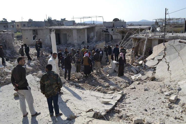 Burgers wandelen tussen de restanten van hun woningen, nadat die vernield werden door een clusterbom.