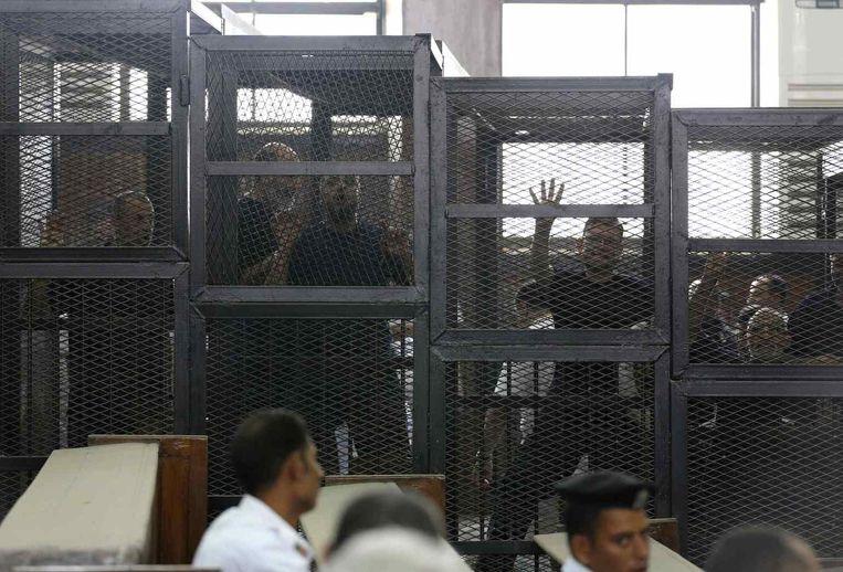 Gevangen leden van de Moslimbroederschap tijdens hun proces in Caïro. Beeld reuters