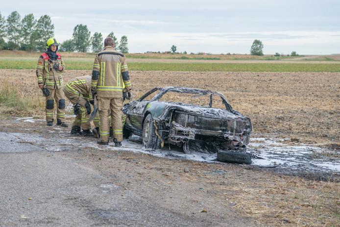 Brandweerlieden staan naast de volledig uitgebrande auto.