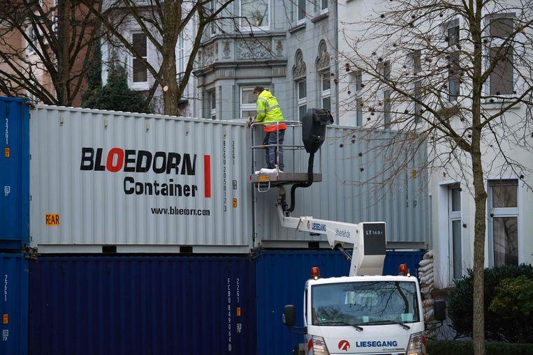 Een muur van containers wordt opgebouwd in Dortmund om huizen te beschermen tegen de WOII-bommen.