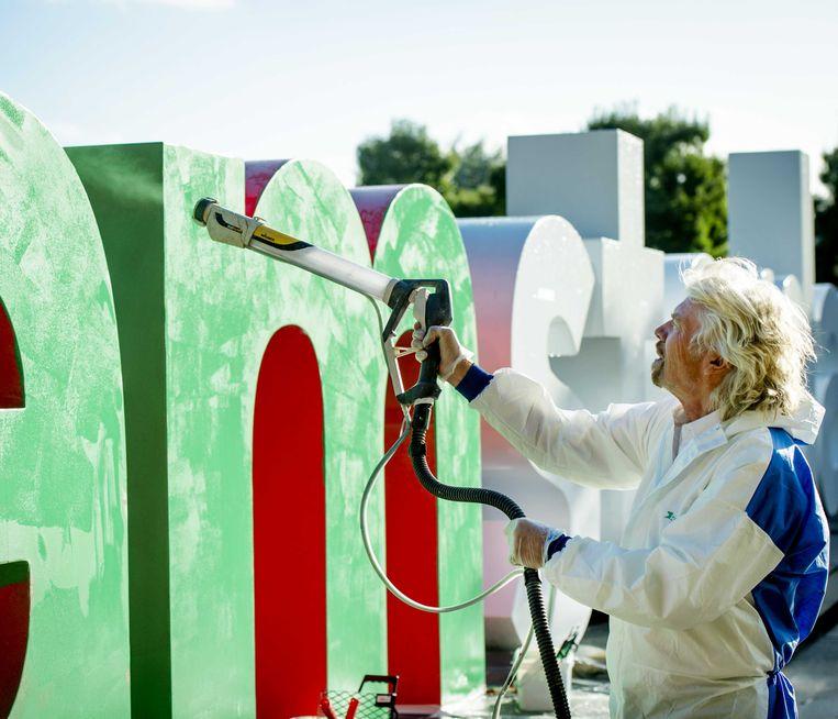 Virgin-oprichter Richard Branson spoot in 2013 het I Amsterdam-logo groen ter gelegenheid van de finale van de Postcode Lottery Green Challenge, een internationale wedstrijd voor startende groene ondernemers. Branson is juryvoorzitter. Beeld ANP