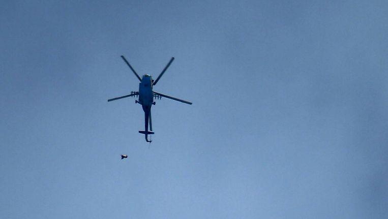 Een legerhelikopter laat een bom vallen in Oost-Ghouta. Beeld AFP