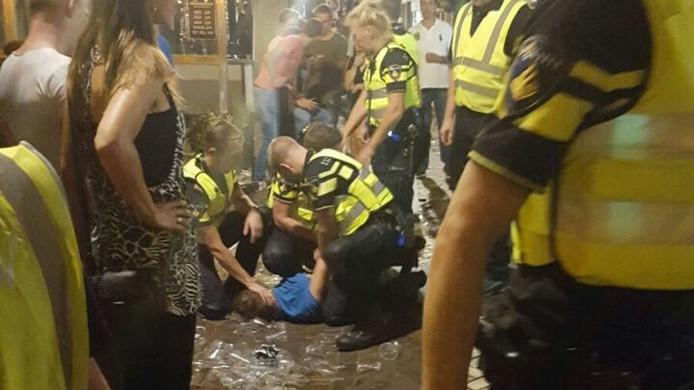 De politie verricht een aanhouding in het centrum van Almelo, in de nacht na de Profronde.