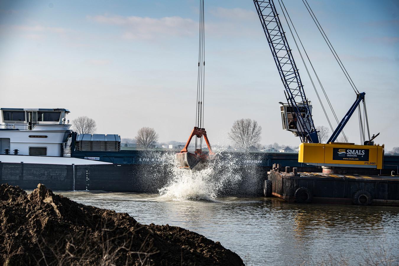 Het storten van een lading in natuurplas Over de Maas bij Alphen.