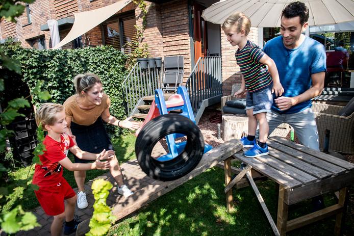 Stefanie en Ronald Bouwels spelen met hun kinderen in de voortuin.