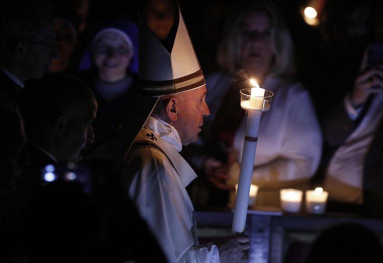 De paus stapt de donkere basiliek in met een kaars.