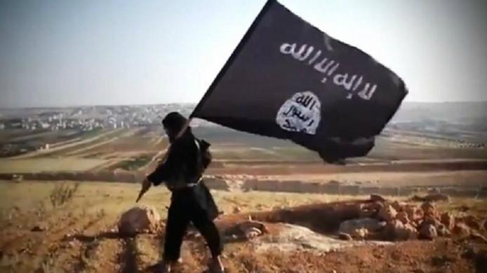 Een IS-strijder loopt met een IS-vlag.