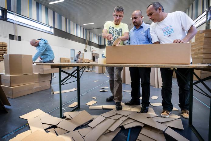 Dirk D'Hondt (links) werkt samen met vluchtelingen Osama en Tofek aan een 'Grossetête'.