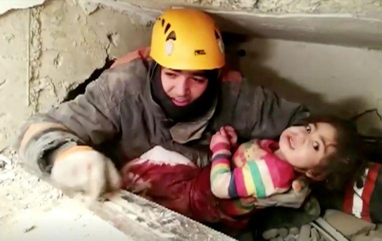 Een man haalt een kind vanonder het puin.