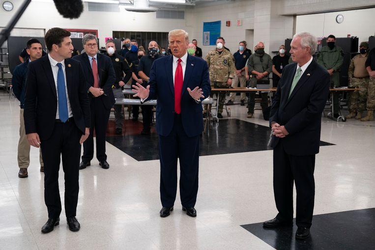 President Donald Trump spreekt met veiligheidsagenten over het geweld in Kenosha (Wisconsin) op een als crisiscentrum ingerichte school. Beeld AP