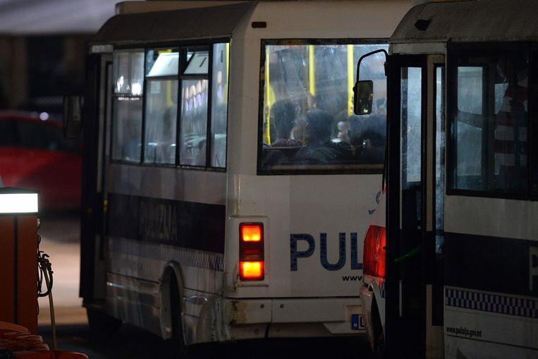 Migranten die van de Alan Kurdi afkomen, worden in politiebusjes weggebracht.